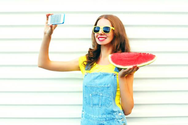 hübsches mädchen mode mit einer wassermelone übernahme einen weißen hintergrund bild selfie auf dem smartphone - jeans overall stock-fotos und bilder