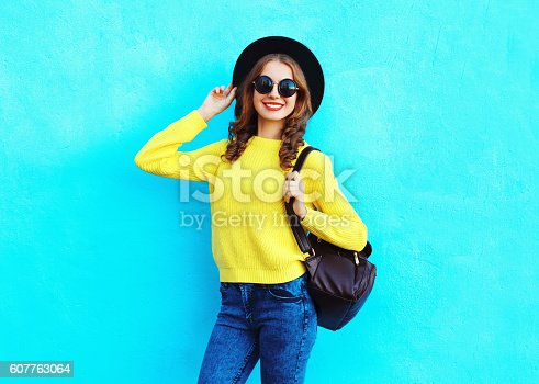 istock Fashion pretty smiling woman wearing black hat yellow knitted sweater 607763064