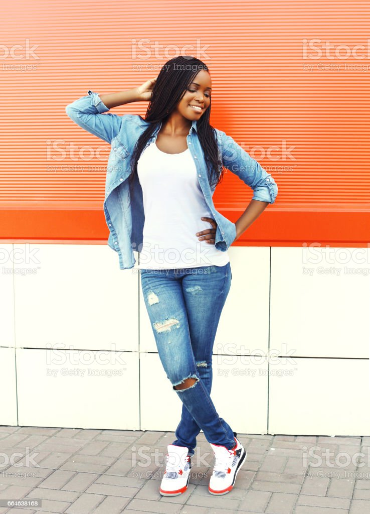 Fashion pretty smiling young african woman in the city over red background stock photo