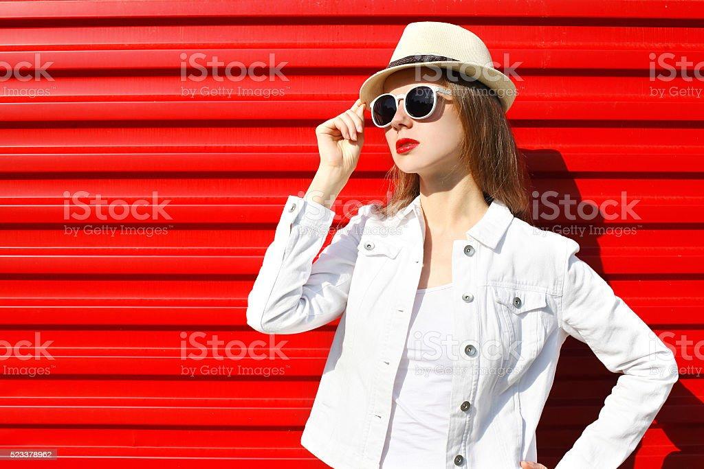 2a286b5b7 Moda bela mulher em óculos de sol, chapéu colorido sobre vermelho foto de  stock royalty