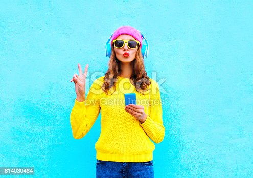 istock Fashion pretty woman listening music in headphones with smartphone colorful 614030464