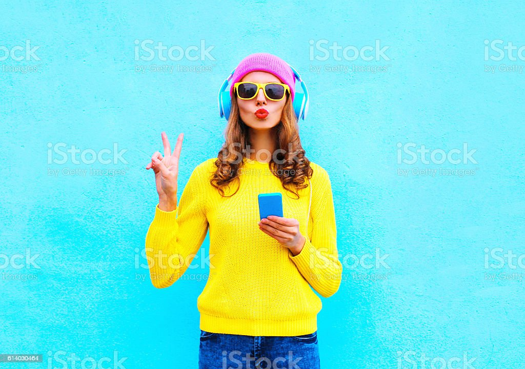 Fashion pretty woman listening music in headphones with smartphone colorful - foto de acervo
