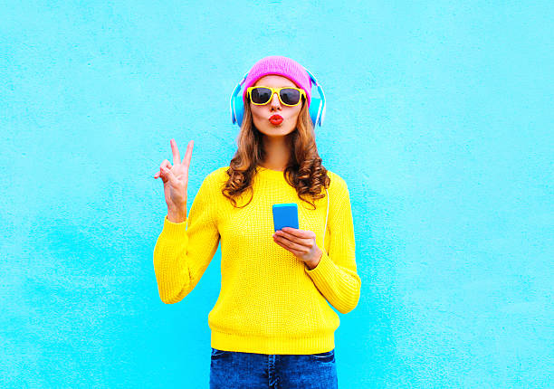 fashion pretty woman listening music in headphones with smartphone colorful - hipster persoon stockfoto's en -beelden