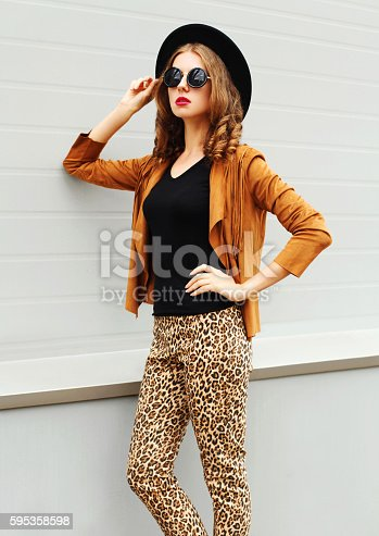 istock Fashion pretty woman model wearing a black hat, sunglasses jacket 595358598