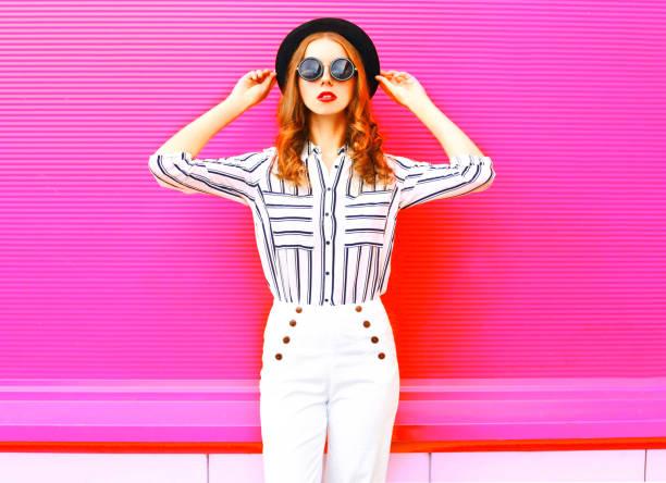 Hübsche Frau Fotomodell trägt schwarzen Hut Sonnenbrille weiße Hosen über bunte rosa Hintergrund – Foto