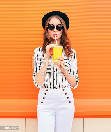 istock Fashion pretty woman model with fresh fruit juice cup 615594472