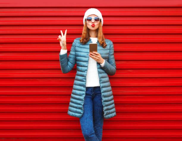 hübsche frau mode mit smartphone hält in den händen auf einem roten hintergrund in der stadt - damenjacken stock-fotos und bilder