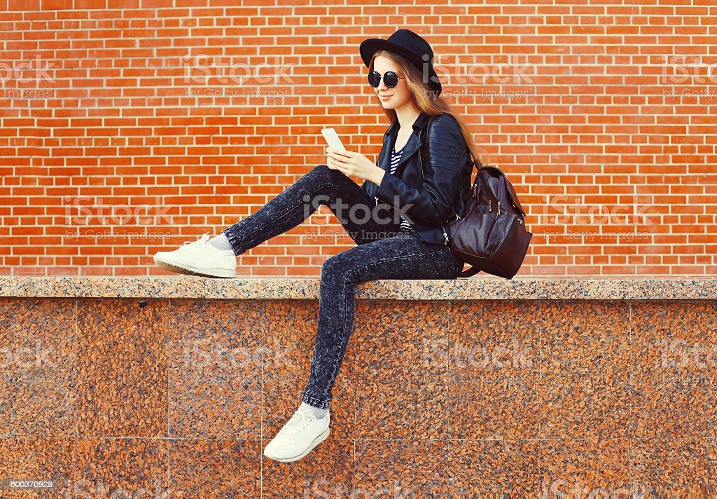 ファッションの可愛らしいを使用する女性スマートフォンでロックブラックスタイル ストックフォト