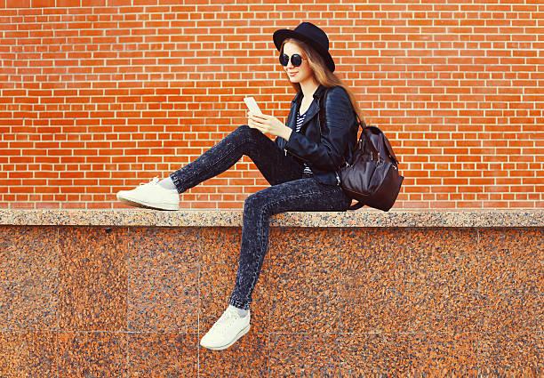 ファッションの可愛らしいを使用する女性スマートフォンでロックブラックスタイル - 秋のファッション ストックフォトと画像