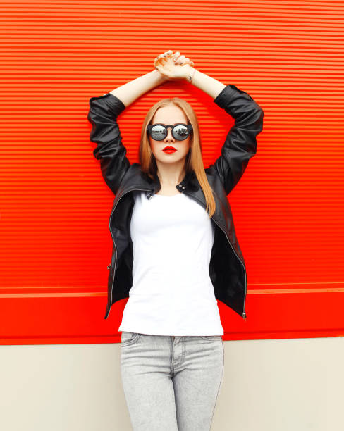 fashion pretty woman wearing a rock black jacket and sunglasses in city over red background - white tshirt stock photos and pictures