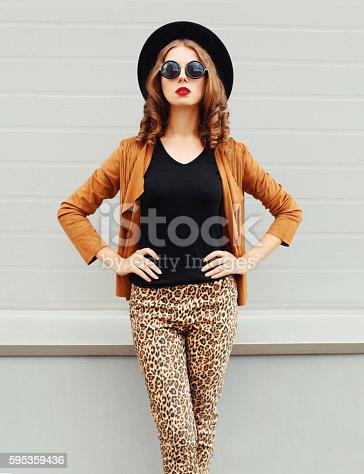 istock Fashion pretty woman wearing black hat, sunglasses, jacket over background 595359436
