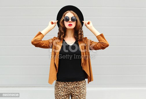 istock Fashion pretty woman wearing black hat, sunglasses, jacket over background 595359538