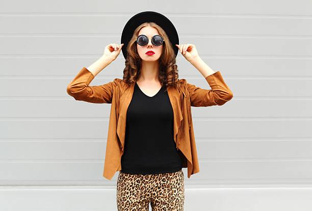 fashion pretty woman wearing black hat, sunglasses, jacket over background - bedruckte leggings stock-fotos und bilder