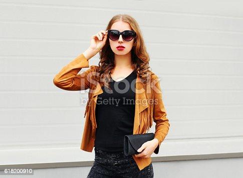istock Fashion pretty woman wearing sunglasses, brown jacket and black handbag 618200910