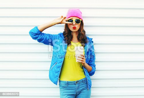 istock Fashion pretty woman with coffee cup in colorful clothes 603863070