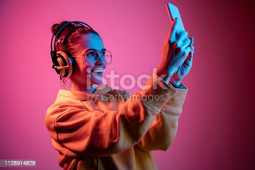 Fashion pretty woman with headphones listening to music and making selfie photo over red neon background at studio.
