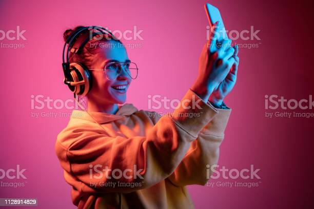 Fashion pretty woman with headphones listening to music over neon picture id1128914829?b=1&k=6&m=1128914829&s=612x612&h=38sq1cgo1nav0h fe2ctdwow4icyadszz2olz ad5zm=