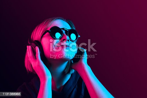 Happy pretty woman with headphones listening to music over red neon background at studio.