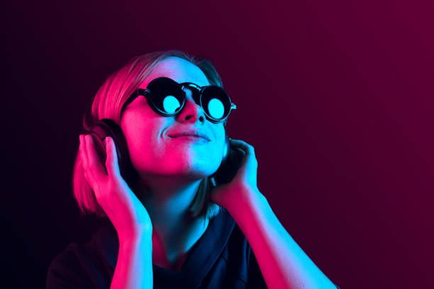 mode vacker kvinna med hörlurar lyssnar på musik över neon bakgrund - lyssna bildbanksfoton och bilder