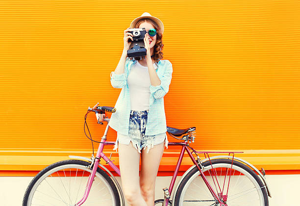 Fashion pretty woman with retro camera and bicycle over colorful stock photo