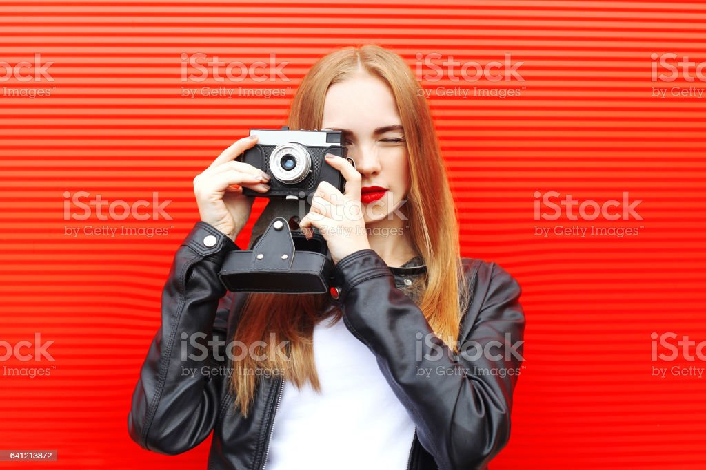 Fashion pretty woman with vintage camera in city over red background stock photo