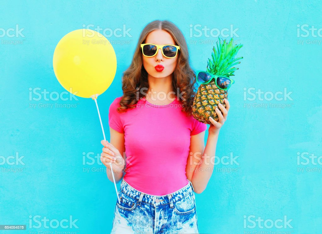 Fashion pretty woman with yellow air balloon and pineapple wearing a pink t-shirt over colorful blue background - Photo