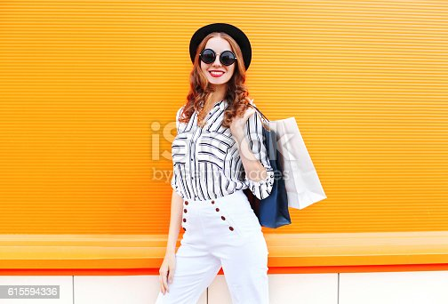 istock Fashion pretty young smiling woman model with shopping bags 615594336