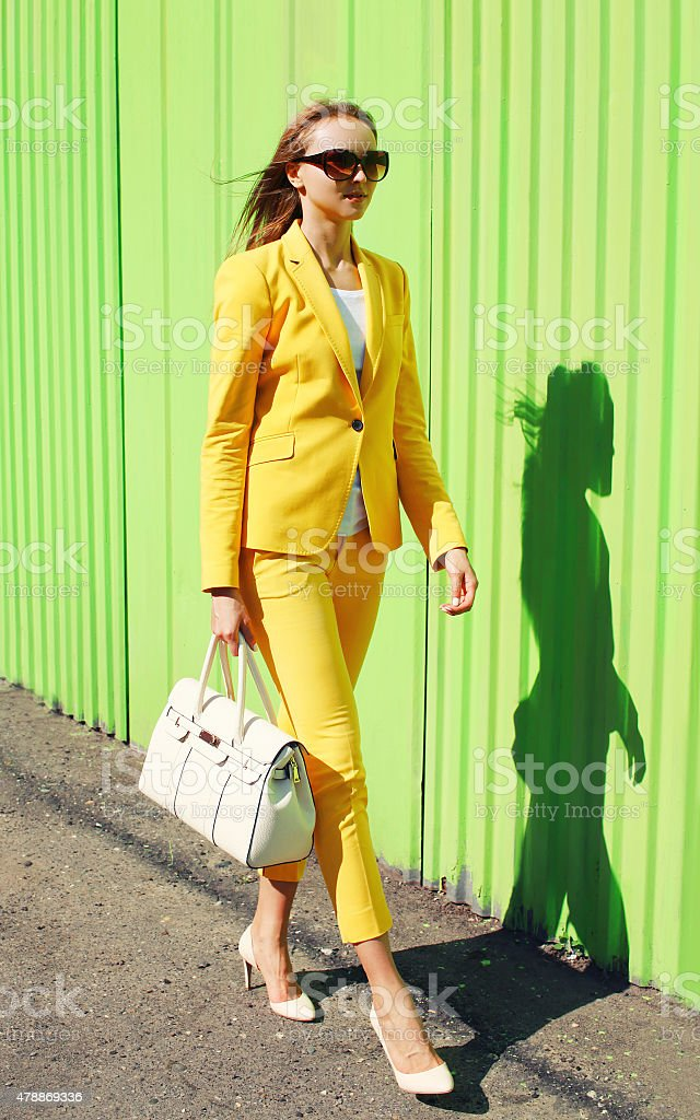 0a47d004a Moda jovem Mulher bonita em Fato amarelo roupas com Mala foto de stock  royalty-free
