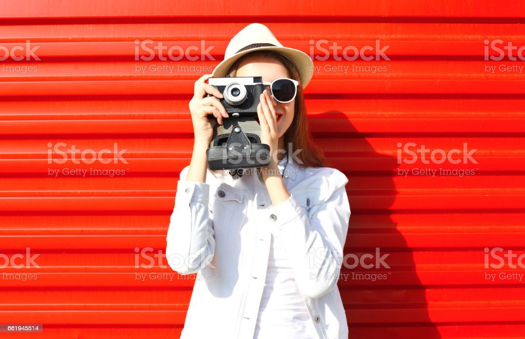Fashion pretty young woman taking picture on retro camera over colorful red background stock photo