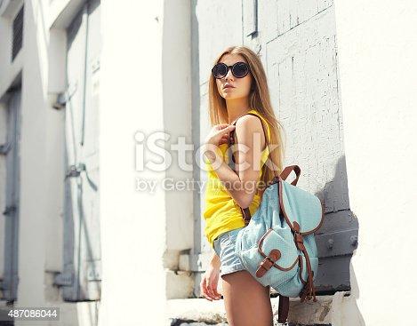 cffda25974 487086034istock Moda hermosa mujer joven lleva gafas de sol y en una  mochila 487086044