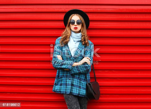 istock Fashion pretty young woman wearing black hat coat jacket handbag 618198612