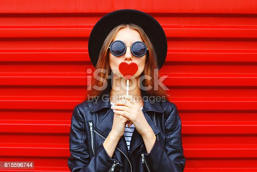 529664088istockphoto Fashion pretty young woman with red lollipop heart wearing black 615596744