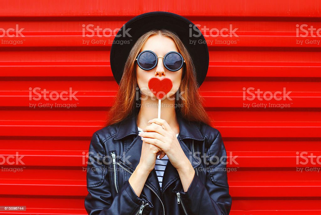Fashion pretty young woman with red lollipop heart wearing black stock photo