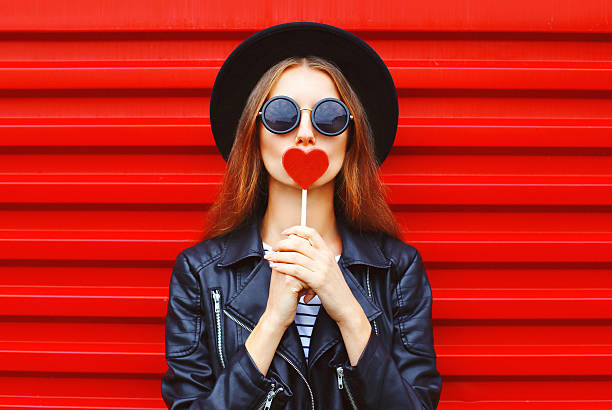 Fashion pretty young woman with red lollipop heart wearing black - Photo