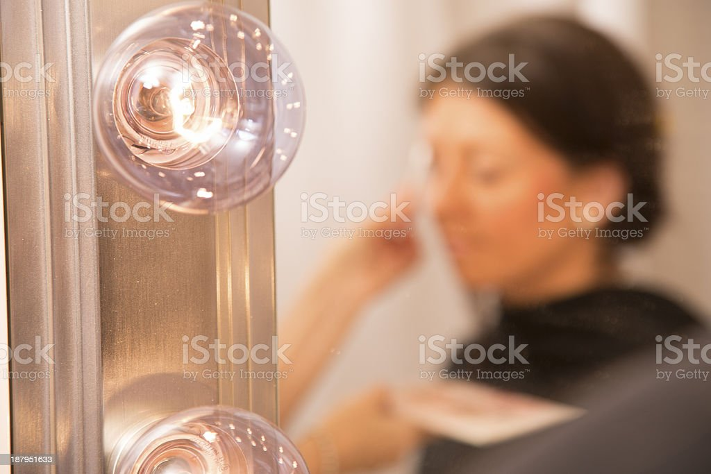 Fashion:  Reflection of woman having makeover in hollywood make-up mirror. royalty-free stock photo