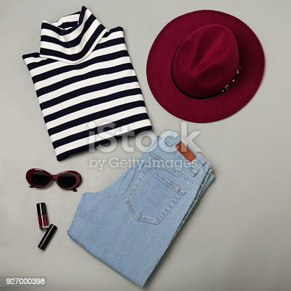 istock Fashion set of blue jeans, striped sweater, burgundy hat and sunglsses. Flat lay. 927000398
