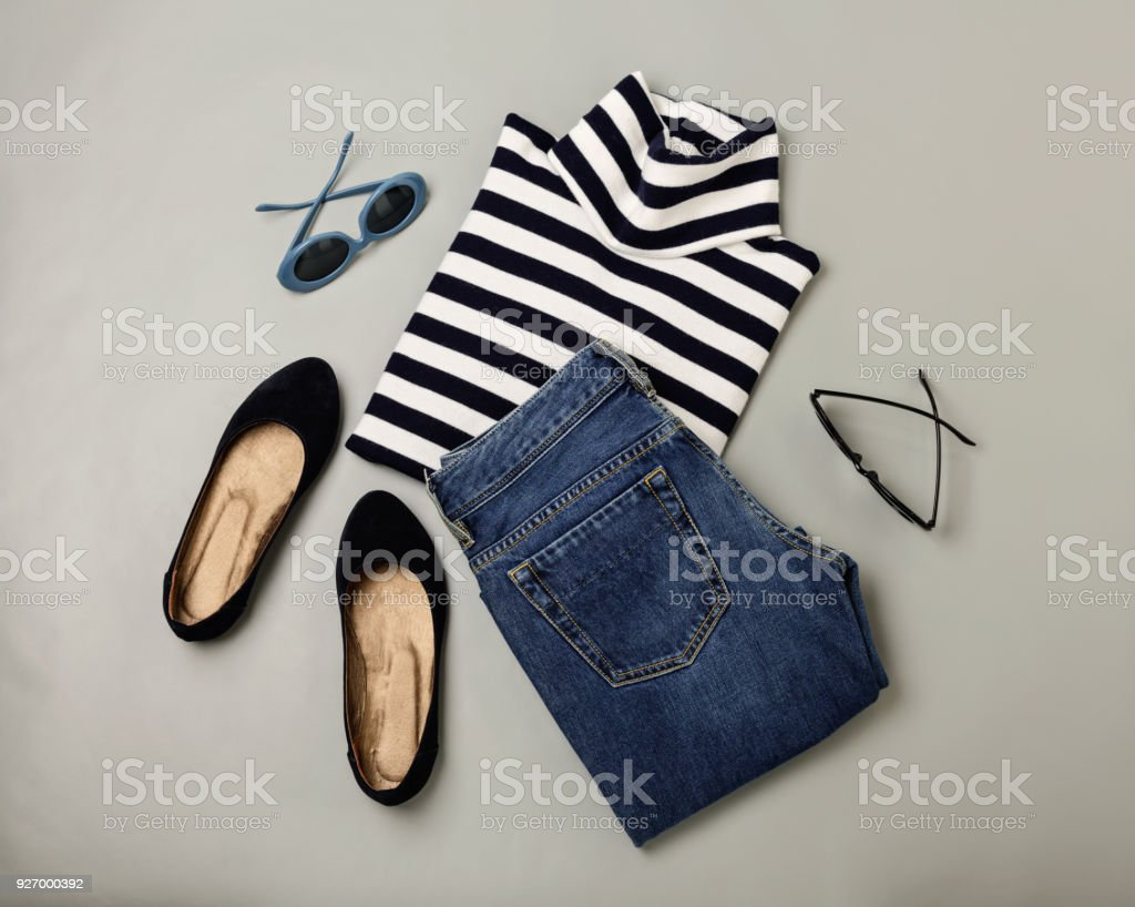 Fashion set of blue jeans, striped sweater, shoes and sunglsses. Flat lay.