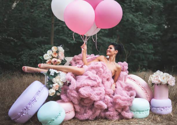 mode sexy frau in rosa atemberaubenden kleid umgeben von französisch macarons gekleidet - spitzenkekse stock-fotos und bilder