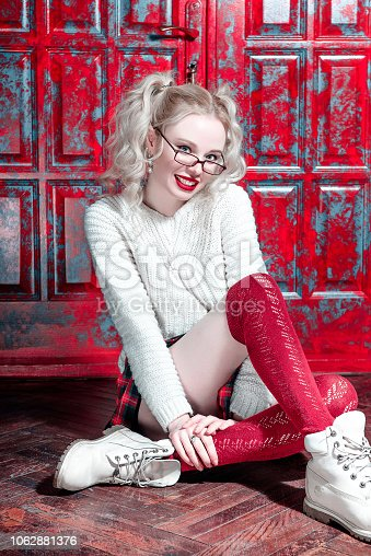 istock Fashion shot of a blonde girl wearing modern youth clothes. College, school style. Hipster girl wearing glasses by a brick wall. Youth fashion. 1062881376
