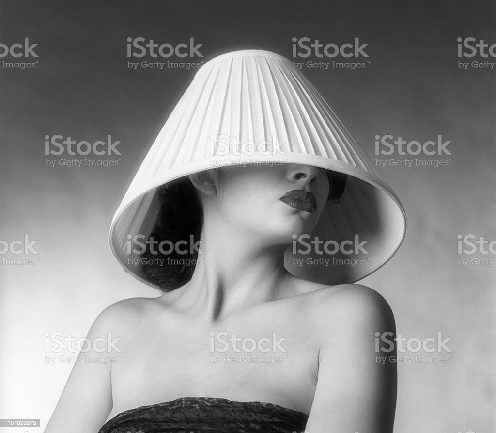 A fashion shot of a woman with a lampshade on her head royalty-free stock photo