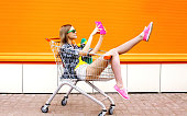 Fashion smiling hipster woman having fun taking picture self-portrait on the digital tablet pc wearing a sunglasses with skateboard sitting in the shopping trolley cart outdoors