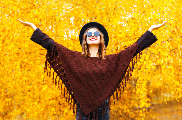 Fashion smiling woman enjoys an autumn park in black round hat, knitted poncho stock photo