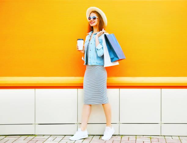 mode, lächelnde frau hält eine kaffeetasse, einkaufstaschen tragen einen strohhut auf orangem hintergrund - kaffee shop stock-fotos und bilder