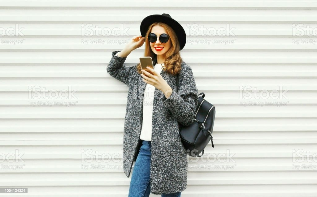 Fashion smiling woman using smartphone on white wall background