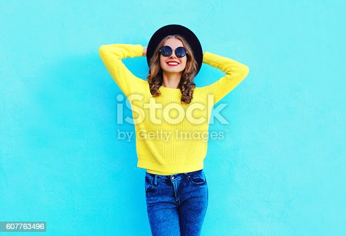 istock Fashion smiling woman wearing black hat and yellow knitted sweater 607763496