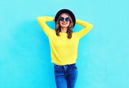 Fashion smiling woman wearing black hat and yellow knitted sweater