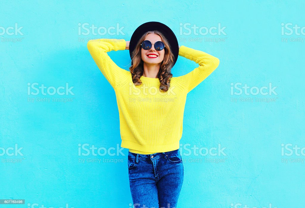 Fashion smiling woman wearing black hat and yellow knitted sweater stock photo