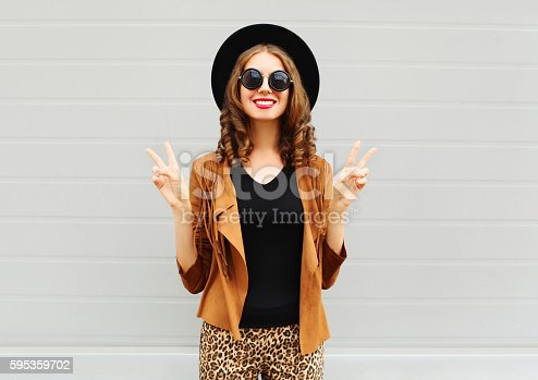istock Fashion smiling woman wearing hat, sunglasses and jacket over background 595359702