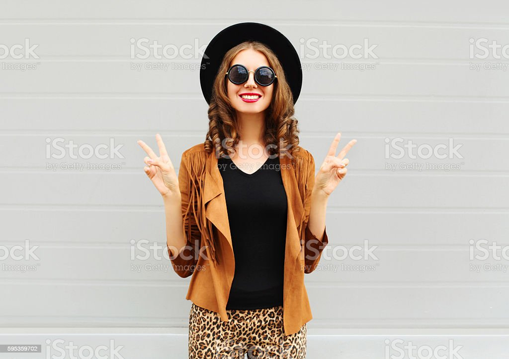 Fashion smiling woman wearing hat, sunglasses and jacket over background stock photo