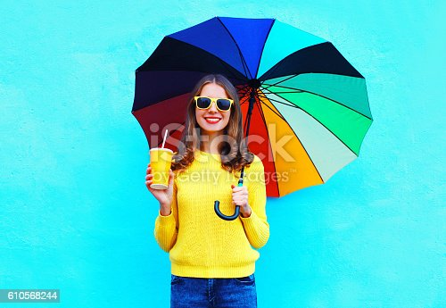 istock Fashion smiling woman with juice cup colorful umbrella in autumn 610568244